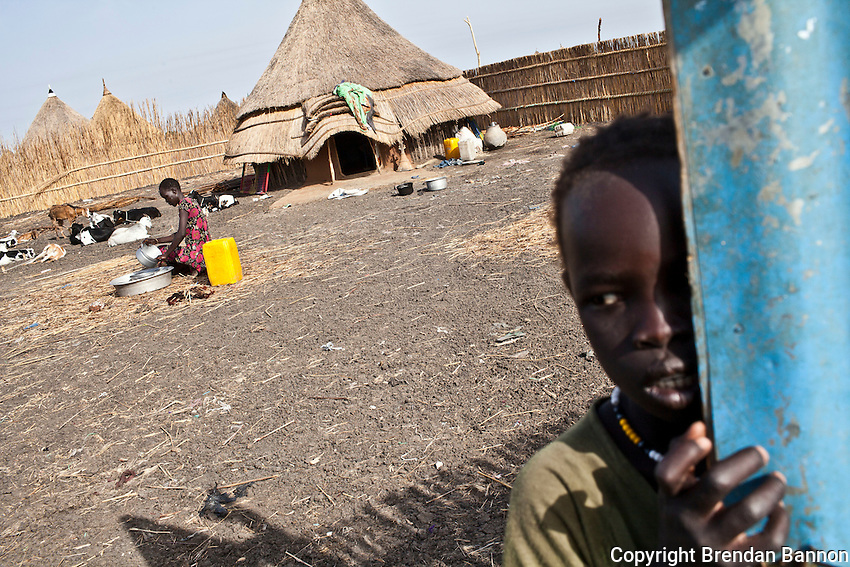 Displaced woman Nyabok Yien washes pots and pans as her children play on the compound of thier host. Nyabok Yien, 30 years old, fled to Nasir to escape attacks in Jonglei state with 5 children. She explains ?I come from Ulak. It was attacked in March [2012], on the same day as Dengjok village. When Ulak was attacked, many people died in the attack. Those who came to attack Ulak killed many people, children, women and even men. That is why we came to Nasir. The fighting happened between the Lou Nuer in Akobo and the Murle, which killed all the children and women. They are not leaving any person, which is why we came here. Only the men remain in Akobo..I left after the attack. My husband died last year, so I came here with my five children. I came with a boat. It took 2 days by boat. I did not have to pay, as it was the government?s boat.?..?I did not bring anything with me. All my belongings were taken by those who attacked Ulak. Five people from my family were killed in the attack.?..?When we arrived in Nasir, all the people welcomed us. I came here because these people are my family. People went to join their parents, because the people form Akobo and from Nasir are one family. I am living with my aunty. 5 adult men and 4 adult women, with many children, now live in this compound.?