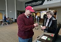 Bill Warren (left) receives an I Voted sticker from Mildred Webster, co-supervisor, Tuesday, February 11, 2020,  at Trinity Fellowship Assembly of God voting center in Fayetteville. Tuesday was the Fayetteville School District's election in which the district was seeking approval of a bond restructuring that will provide $111 million for maintenance projects districtwide as well as some new construction projects.