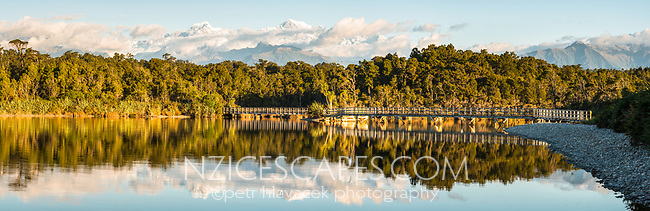Southern Alps and board walk bridge reflecting in Gillespies Lagoon, Westland Tai Poutini National Park, West Coast, South Westland, UNESCO World Heritage Area, New Zealand, NZ
