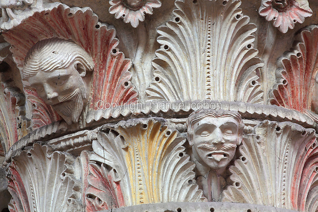 Carved polychrome Romanesque capital, 12th century, with human faces peering out of foliage of acanthus leaves, one sticking out his tongue, in the nave of the Cathedrale Saint-Julien du Mans or Cathedral of St Julian of Le Mans, Le Mans, Sarthe, Loire, France. The cathedral was built from the 6th to the 14th centuries, with both Romanesque and High Gothic elements. It is dedicated to St Julian of Le Mans, the city's first bishop, who established Christianity in the area in the 4th century AD. Picture by Manuel Cohen