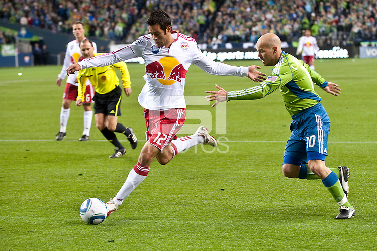 New York Red Bulls defender Mike Petke (12) drives the ball downfield against Freddie Ljungberg (r) of the Seattle Sounders. The Sounders lost to the New York Red Bulls, 1-0, in an MLS match on Saturday, April 3, 2010 at Qwest Field in Seattle, WA.