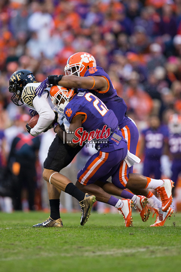 K.J. Brent (80) of the Wake Forest Demon Deacons drags two Clemson Tigers defenders for extra yards after catching a pass during first half action at Memorial Stadium on November 21, 2015 in Clemson, South Carolina.  The Tigers defeated the Demon Deacons 33-13.   (Brian Westerholt/Sports On Film)