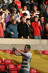 Nottingham Forest 2 Yeovil Town 5, 18/05/2007. City Ground, League One Play Off Semi Final 2nd Leg. A supporter of Yeovil Town taking a photograph of fellow fans before his club's League One play-off semi-final match against Nottingham Forest at the City Ground. Forest had won the first leg by 2 goals to nil at Yeovil the previous week but were defeated by 5 goals to 2 after extra time and missed out on the play-off final at Wembley. Yeovil went on to play Blackpool in the final for the one remaining promotion place to the Championship. Photo by Colin McPherson.