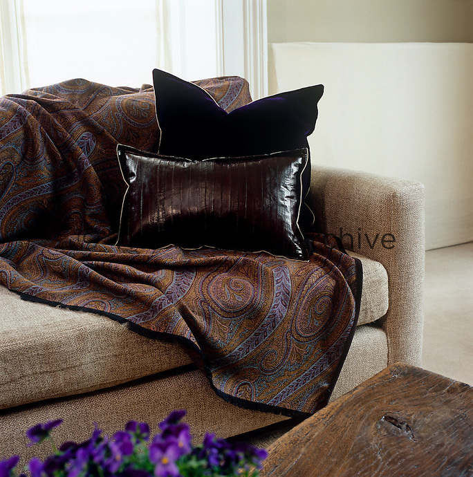 In the living room a paisley throw and leather and velvet cushions in deep plum and chocolate have been juxtaposed to stunning effect