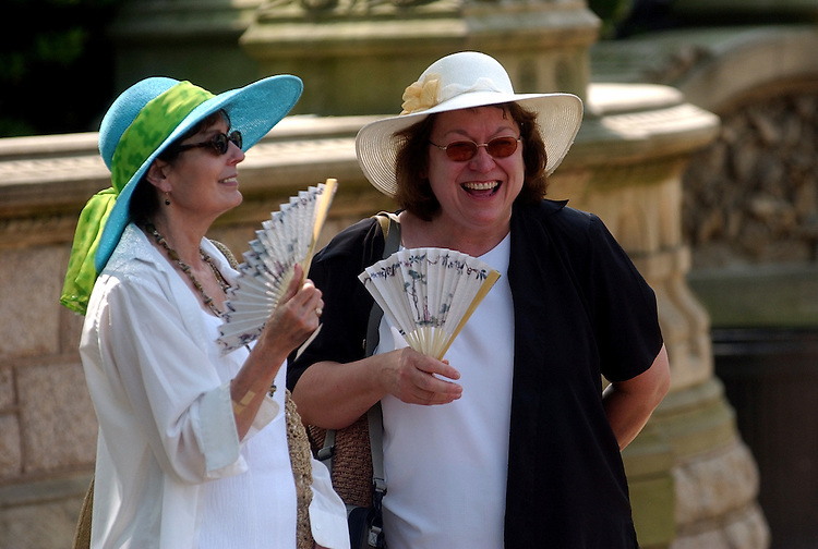 Carlotta Litten, and Kathy Metcalf, tourists visiting the Capitol from the midwest, cool off in the heat with fans on the West Front.