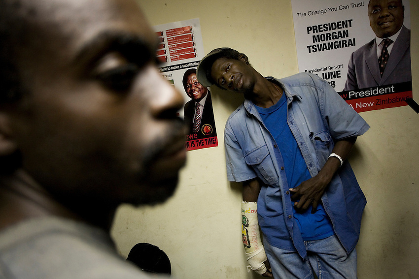 An MDC supporter whose arm was broken by Robert Mugabe's Zanu-PF thugs leans against a wall covered by Morgan Tsvangirai campaign posters at Harvest House, the MDC headquarters, in Harare, Zimbabwe, Monday, June 23, 2008.