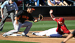 Diamondbacks' Marc Krauss slides safely under the tag of Giants' Chris Dominguez during a Cactus League preseason game between the San Francisco Giants and the Arizona Diamondbacks in Scottsdale, Ariz., on Sunday, March 4, 2012. .Photo by Cathleen Allison