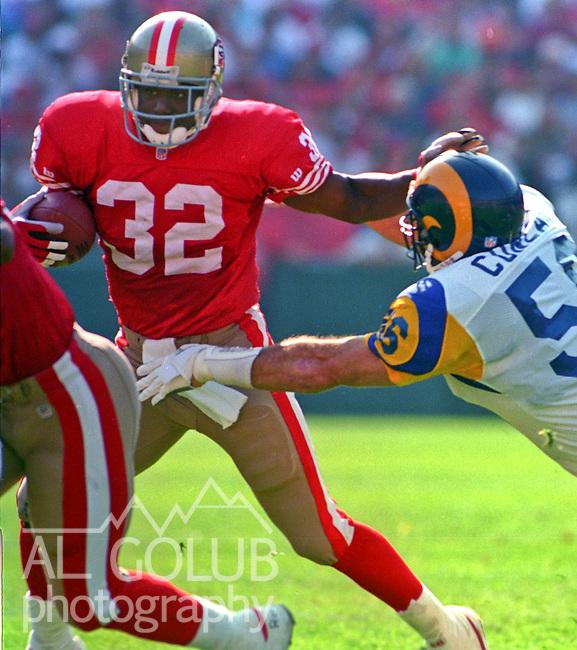 San Francisco 49ers vs. Los Angles Rams at Candlestick Park Sunday, October 31, 1993.  49ers beat Rams 40-17.  San Francisco 49ers running back Ricky Watters (32) straight arms Los Angles Rams linebacker Shane Conlan (56).