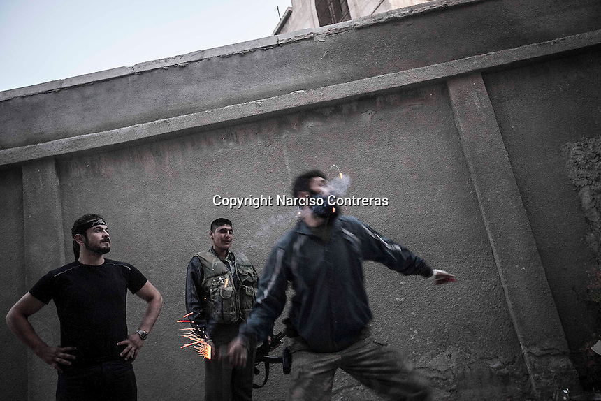 In this Sunday, Oct. 28, 2012 photo. A rebel fighter throws a homemade grenade over the Syrian army troops at the front line in Bustan Al-Pasha in Alepppo, the Syrian's largest city. (AP Photo/Narciso Contreras).