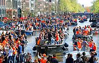 Koningsdag in Amsterdam. De grachten kleuren oranje. Boten op de prinsengracht