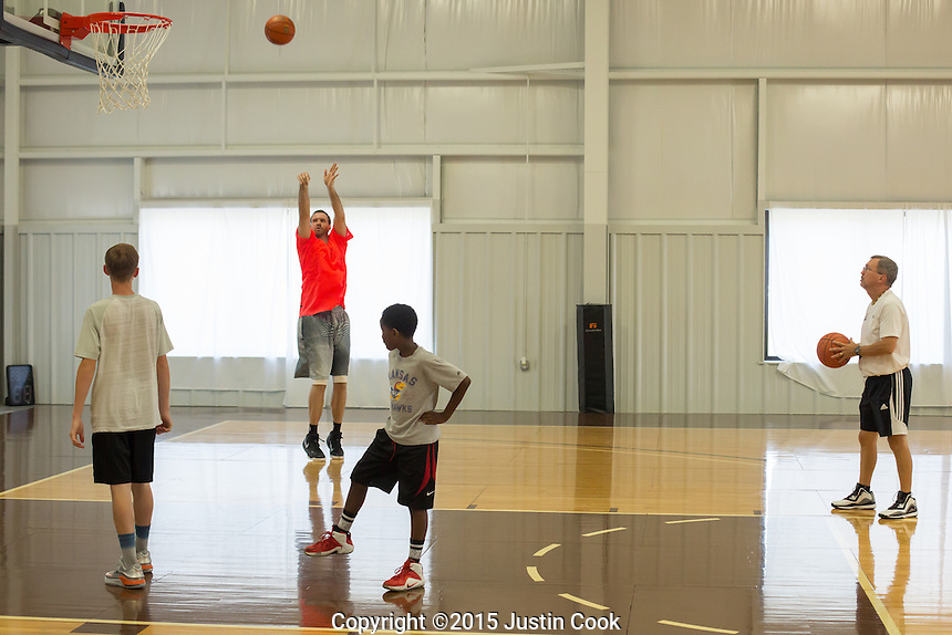 Shavlik shoots over Nate Yow, 14 (left) and T.J. Southerland, 10, (RIGHT) and his coach Mike Hollis (FAR RIGHT) keeps time during practice in Sanford, N.C. on Friday, June 26, 2015. (Justin Cook)