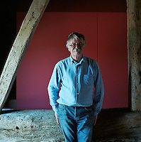 Portrait of architect David Pocknell leaning against a large wooden beam