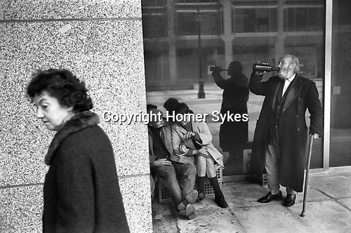 Two old wino's tramps enjoy a drink and chat with female homeless woman. Victoria, London 1976.