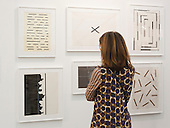 London, England. 14 October 2014. Woman looking at artworks by Kishio Suga. Frieze Art Fair 2014 opens in Regent's Park, London. Photo: Bettina Strenske