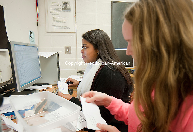 TORRINGTON,  CT-122214JS04- Torrington High School journalism students Aeliana Dorso, 16, left, and Jessica Gray, 16, tally up subscriptions for the school paper, The Raider Times, during class on Monday. The newspaper is back after a one-year absence due to budget cuts. <br />  Jim Shannon Republican-American