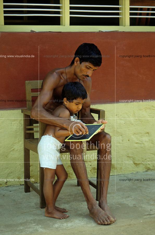 INDIA Karnataka Taccode, farmer and his son at home works for school at a farm near Mangalore / INDIEN Bauer und Sohn bei Schulaufgaben auf einem Bauernhof