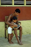 INDIA Karnataka Taccode, farmer and his son at home works for school at a farm near Mangalore / INDIEN Bauer und Sohn bei Schulaufgaben auf einem Bauernhof