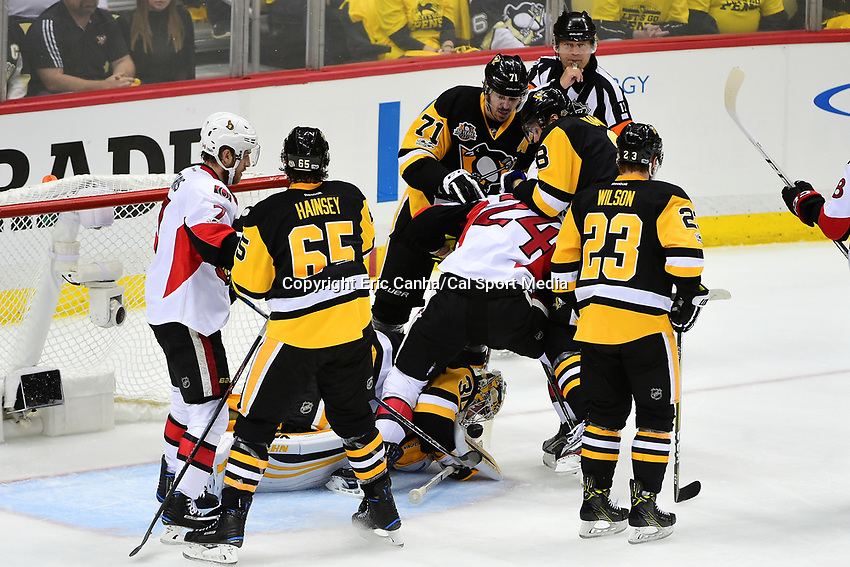 May 25, 2017: Pittsburgh Penguins goalie Matt Murray (30) fights at the bottom of the pile to control the puck during game seven of the National Hockey League Eastern Conference Finals between the Ottawa Senators and the Pittsburgh Penguins, held at PPG Paints Arena, in Pittsburgh, PA. The Pittsburgh Penguins defeat the Ottawa Senators 3-2 in double overtime to win the NHL Eastern Conference Championship and advance to face the Nashville Predators in the Stanley Cup Finals.  Eric Canha/CSM