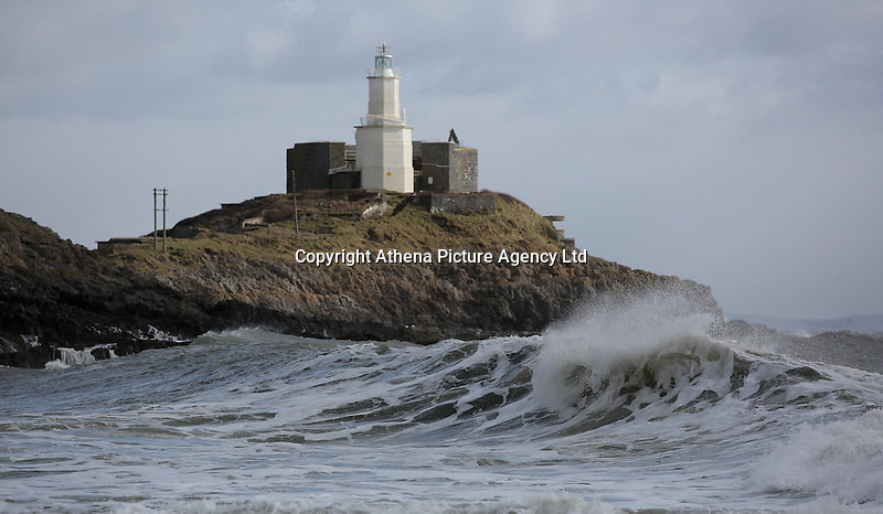 """WEATHER PICTURE WALES<br />Pictured: Waves crashing against rocks against Mumbles Lighthouse in Bracelet Bay, near Swansea, Wales. Wednesday 02 March 2016<br />Re: Roads have been closed, homes left without power and tiles blown from roofs after Storm Jake brought wintry showers and high winds to Wales.<br />Yellow Met Office """"be aware"""" warnings of snow, ice and wind were issued for most of Wales for Wednesday morning.<br />Gusts - forecast to reach up to 70mph - caused roof tiles to fall and trees to be blown over in Aberystwyth, with roads closed as a precaution."""