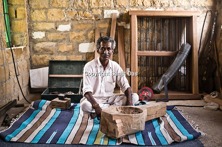 50year old, Sankara Ram, a local carpenter and a Kamancha maker poses with a unfinished Kamancha in his workshop in Hamira village of Jaiselmer district in Rajasthan, India. Photo: Sanjit Das/Panos