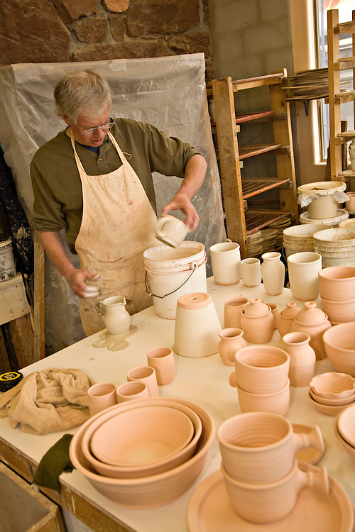 Adult man glazing pottery
