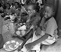 "Children eat lunch in their ""classroom"" at the International Committee of the Red Cross orphange, clinic and school in Mogadishu, Somalia, Feb 1993. Some of the children wear t-shirts given to them by U.S. Marines depicting a U.S. and Somali flags crossed with a U.S.M.C. emblem in the middle. Un Forces took part in Operation Restore Hope in Somalia in 1992-93 to alleviate famine brought on by drought and civil war."