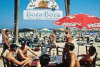 "Spain. Ibiza in the Balearic islands. Ibiza. Mediterranean sea. Beach "" Den Bossa"". Tourists (young men) Have a drink, take a rest and sunbathe at the "" Bora Bora"" café © 1999 Didier Ruef"