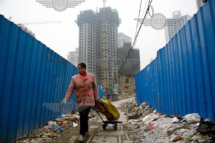 A scavenger walks by a demolished neighbourhood.