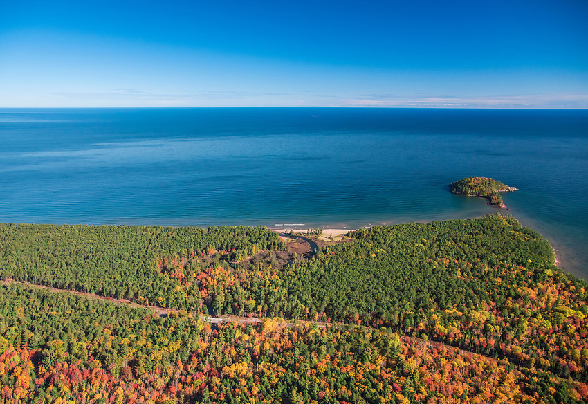 Aerial photography of the rugged Lake Superior shoreline north of Marquette, Michigan during fall color season. Areas shown include County Road 550, Little Presque Isle and Harlow Creek.