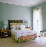 A serene palette in this master bedroom evokes a seascape with the walls covered in a fine sea-blue fabric