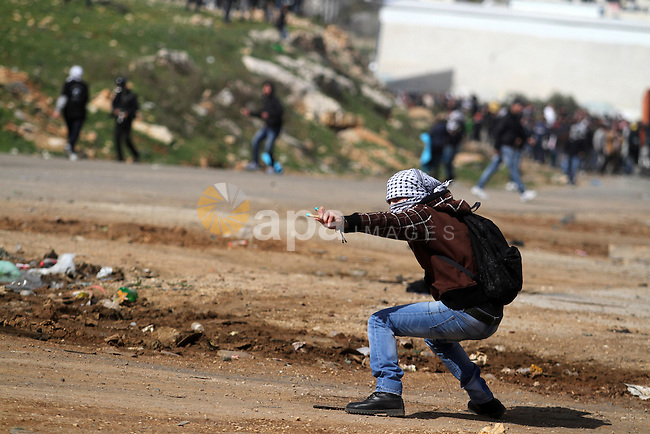 A Palestinian protester throws stones at Israeli soldiers during clashes in front of Ofer prison, near the West Bank city of Ramallah, following a demonstration in support of Palestinian detainee, Samer Issawi, who has been on hunger strike for more than 200 days, and other prisoners on hunger strike in Israeli prisons on February 15, 2013. A United Nations official on February 13, expressed concern about the wellbeing of Palestinian detainees in Israeli prisons and in particular about the condition of Issawi. Photo by Issam Rimawi