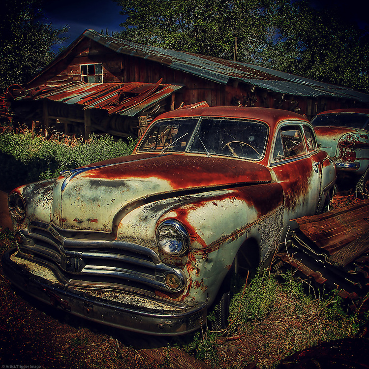 Vintage rusty car abandoned in long grass beside decaying shed