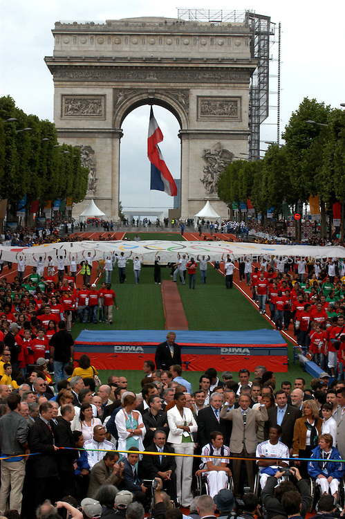 6/5/2005--Paris, France..Bertrand Delanoë (arms raised, tan suit) , Mayor of Paris opens the 'Fetons l'Amour des Jeux' ('Celebrate the love of the Games') event today on the Champs-Elysées which invited members of the public to participate in numerous Olympic sports on Paris's most famous street. Paris has put in an ambitious bid for the 2012 Olympics, competing with New York, Moscow, London and Madrid and considered a lead candidate city...The Champs-Elysées was transformed into a symbolic ?Champs  Olympiques? with 28 Olympic disciplines grouped around a gigantic 700 m athletics track running from the Arc de Triomphe to Avenue  George V. Boxing rings, tennis courts, a rowing  pool and a hockey pitch were also set up..Photograph By Stuart Isett.All photographs ©2005 Stuart Isett.All rights reserved.