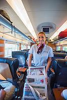 Spain, Costa Brava, Catalonia, Tossa de Mar. Renfe trains. On board staff distributing magazines.