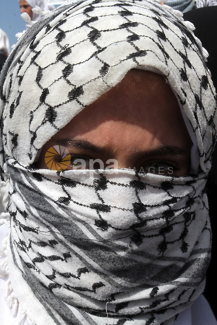 A masked Palestinian schoolgirl looks on during an anti-Israel protest in the southern Gaza Strip town of Rafah on October 14, 2015. Amid violent protests and a wave of stabbings spreading fear in Israel and warnings that a full-scale uprising could erupt, a new generation of Palestinians has been leading the unrest. Photo by Abed Rahim Khatib