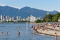 People sunbathing and cooling off in English Bay at Kitsilano Beach, Vancouver, British Columbia, Canada