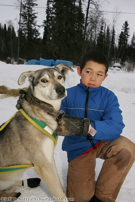 "Anvik resident Damien Jensen holds ""Taos"", a lead dog of Aaron Burmiester's team prior to Aaron leaving his 8 hour mandatory Yukon river layover at the Anvik checkpoint.  2005 Iditarod Trail Sled Dog Race."