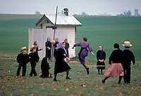 A group of Amish boys and girls play jump rope as a group during recess. The outside bathroom is at the rear. Amish children. Lancaster Pennsylvania United States Amish schoolyard.