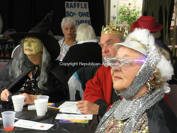 "HARWINTON, CT - 102908KB01 - 29 October 2008 - Gerry Stubbs of Burlington, right, and Priscilla and Fred Kunesch of Torrington wait for Harwinton Senior Center Director Sharlene Copeland to announce the winners in a costume contest during a Halloween party at the center on Wednesday. Stubbs, who was covered head-to-toe in sequined attire, won one of several prizes, as did Fred Kunesch, who was dressed up as a king. ""I don't know what I'm dressed up as,"" Stubbs admitted. Kari Banach Photo"