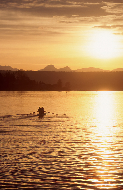 Seattle, Rowers in a pair, sunrise, Lake Washington, Cascade Mountains in distance, Washington State, Pacific Northwest, USA.
