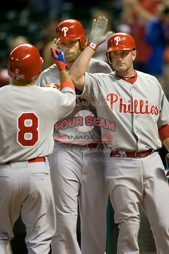 Philadelphia Phillies catcher Brian Schneider and OF Jayson Werth meet Shane Victorino (8) against the Houston Astros on Turn Back the Clock Nite. Game played on Saturday April 10th, 2010 at Minute Maid Park in Houston, Texas.  (Photo by Andrew Woolley / Four Seam Images)