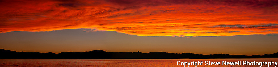 """Burning Sky"" Large Panoramic- The size of this panoramic is can be very large the 24x99"" and 44x182"" are two of the sample sizes.  I captured this amazing sunset over Lake Tahoe from Zephyr Cove Beach located on the Nevada side of South Lake Tahoe on June 8th, 2013. That week the clouds were developing every day with the potential to be a spectacular sunset. Every night I shot from a different location in South Shore with this particular night turning into the most amazing sunset I have ever seen in my 30 years of living here.  The color of the water turned completely red. Normally you have a little color on the clouds and it reflects in the water but on this night it turned the whole entire lake red like I have never seen before anywhere in the world."