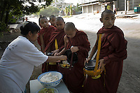 A group of novice monks collect food on their early morning alms round.
