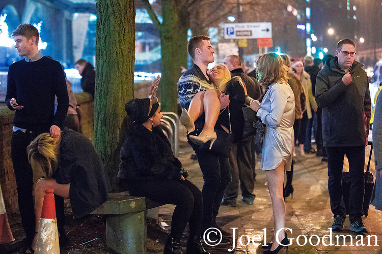 "© Joel Goodman - 07973 332324 . 16/12/2017. Manchester, UK. A man lifts and carries a woman on Deansgate Locks . Revellers out in Manchester City Centre overnight during "" Mad Friday "" , named for historically being one of the busiest nights of the year for the emergency services in the UK . Photo credit : Joel Goodman"
