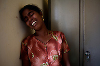 """The young wife of a Tamil man, killed the night before by unknown gun men  cries while interrogated by government police officers in a hospital, near the city of Batticaloa, in Eastern Sri Lanka on Thursday, October 12 2006..The Sri Lanka civil war is an ongoing conflict on the island nation of Sri Lanka Since the 1983 """"Black July""""  pogrom there has been on and off civil war, mostly between the government and the Liberation Tigers of Tamil Eelam, or the LTTE, who want to create an independent state of Tamil Eelam in the north east of the island. It is estimated that the war has left 65000 people dead since 1983 and caused great harm to the population and economy of the country. A cease fire was declared in 2001, but hostilities renewed in late 2005. Following escalation of violence         in July 2006, a senior rebel leader declared the ceasefire null and void, although both sides later reaffirmed their commitment to the ceasefire agreement. Hundreds of people, including military personnel, rebels, and Tamil, Sinhalese and muslim civilians have been killed in fighting this year. Thousands of civilians have been displaced, many coming from areas already stroke by the dec 2004 Tsunami.."""