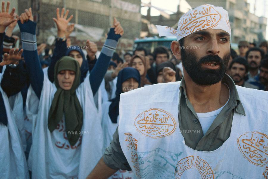 TEHRAN, IRAN - 1979: A demonstration by the supporters of the religious leader of the 1979 Iranian revolution; Ruhollah Musavi Khomeini. The white fabric over their clothes are symbols of the Islamic Burial Shroud to show their great support towards Khomeini and the fact that they are ready for martyrdom in the name of Islam. (Photo by Reza/Webistan)<br /> T&eacute;h&eacute;ran, Iran - 1979.<br /> Une manifestation de soutien du chef religieux de la r&eacute;volution iranienne de 1979 : Ruhollah Musavi Khomeini. L'&eacute;toffe blanche sur leurs habits est un symbole des enterrements islamiques, pour montrer leur soutien &agrave; Khomeini et le fait qu'ils sont pr&ecirc;ts &agrave; devenir martyr au nom de l'islam.