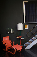 In the living room varying textures of black contrasting with the coral-pink lacquer of the Marcel Breuer chaise-longue have resulted in this stunning corner