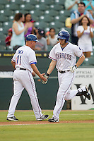 Round Rock Express outfielder Jared Hoying (30) is greeted by coach Spike Owen (11) after blasting a first inning home run in the Pacific Coast League baseball game against the Oklahoma City RedHawks on August 1, 2014 at the Dell Diamond in Round Rock, Texas. The Express defeated the RedHawks 6-5. (Andrew Woolley/Four Seam Images)