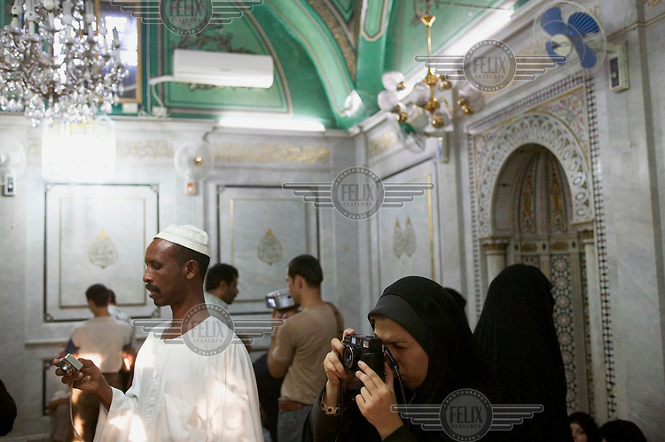 Pilgrims take photographs of the silver shrine that is purported to contain the head of Imam Hussein, the grandson of Prophet Muhammad, at Omayyad Mosque.