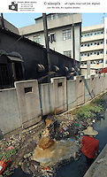 A lady collects waste from a polluted water channel next to a factory in Changping, Guangdong, China. The environment of much of China is suffering as a result of the rapid economic growth causing rampent pollution that the state cannot keep under control..17-DEC-04